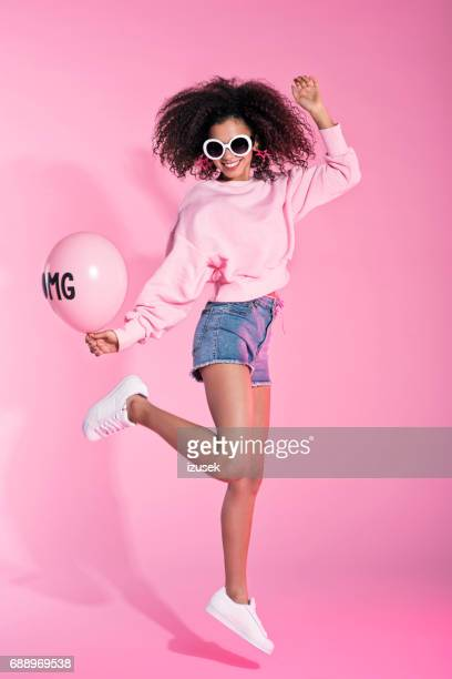 full lenght portrait of young afro woman jumping - denim shorts stock pictures, royalty-free photos & images