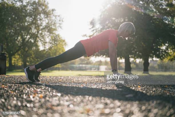 full length action portrait of sportswoman doing push-ups - clapham common stock pictures, royalty-free photos & images