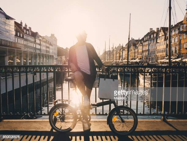 Full length back lit of man standing with bicycle and shopping bags on footbridge in city