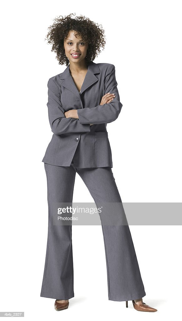 full length business portrait of a young adult woman in a grey suit as she folds her arms and smiles : Foto de stock