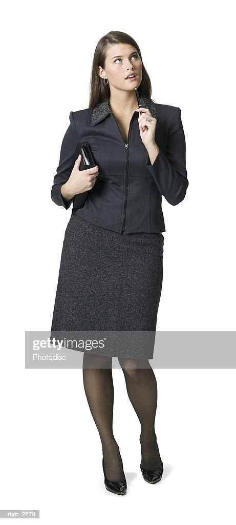 full length business shot of a young adult woman in a dark outfit as she thinks : Foto de stock