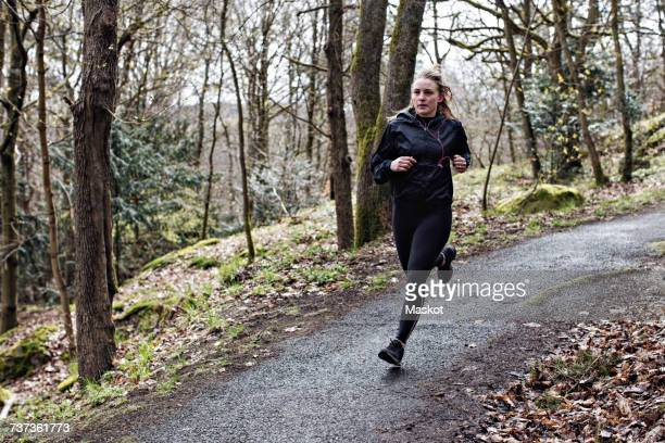 Full length determined female athlete running on narrow road in forest