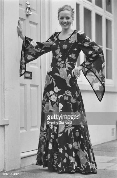 Full length evening dress in a floral fabric with trumpet sleeves, UK, 1st August 1973.