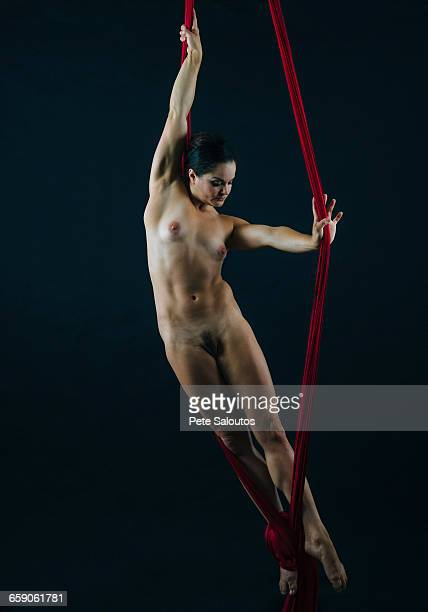 Full length front view of nude aerial dancer with red silk ropes