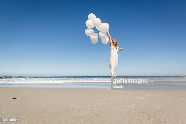 Full length front view of woman jumping on beach wearing white dress holding balloons