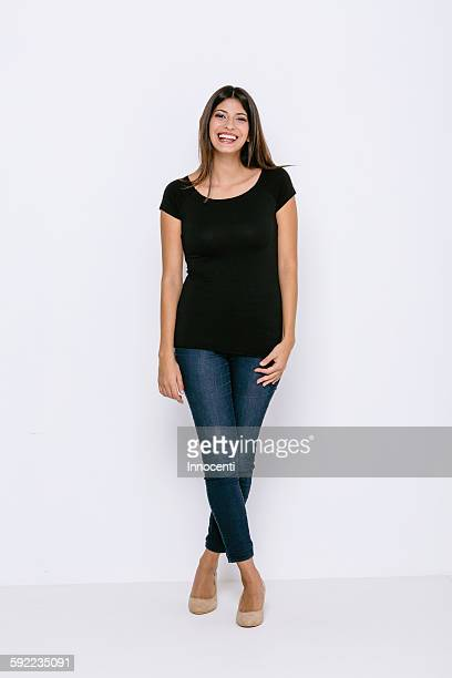full length front view of young woman standing legs crossed looking at camera smiling - zuid europese etniciteit stockfoto's en -beelden