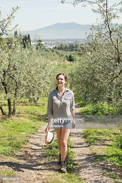 Full length front view of young woman walking on dirt track looking away smiling