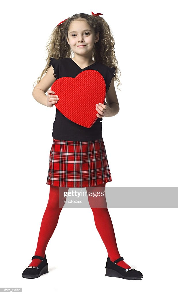full length holiday portrait of a young female child as she holds up a heart box of chocolates : Foto de stock