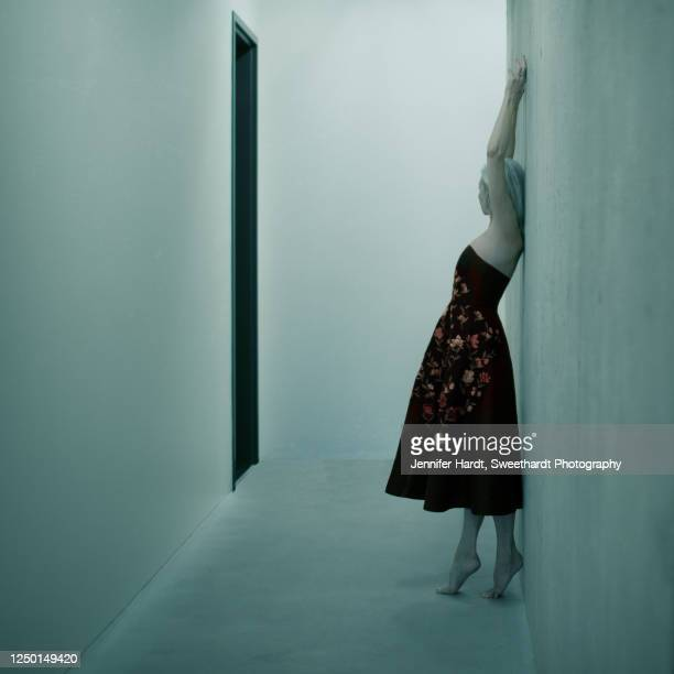 full length image of a woman leaning against a wall on her tiptoes - strapless dress stock pictures, royalty-free photos & images