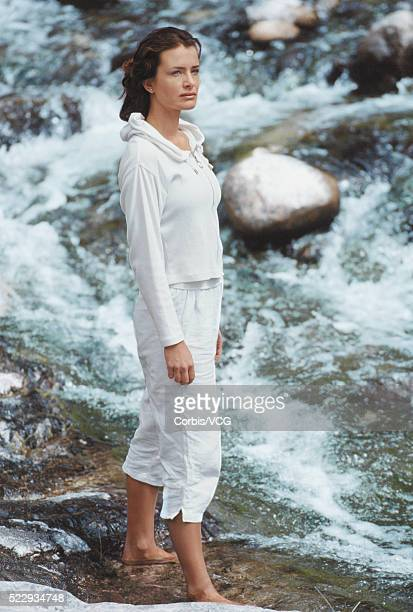 full length image of a woman standing in a rocky bay - vcg stock pictures, royalty-free photos & images