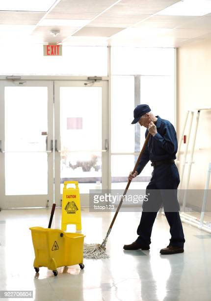full length image of senior man working as a janitor in building. - janitor stock photos and pictures
