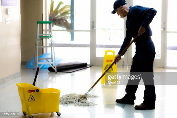 full length image of senior man working as a janitor in building. - commercial cleaning stock photos and pictures