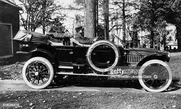 Full length landscape shot of Packard car with an African American chauffeur, outdoors, 1920. .