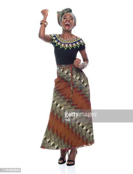full length of 20-29 years old african ethnicity / african-american ethnicity young women / female in front of white background wearing headscarf / dress / traditional clothing who is smiling / happy / cheerful / excited / successful - 25 29 years stock pictures, royalty-free photos & images
