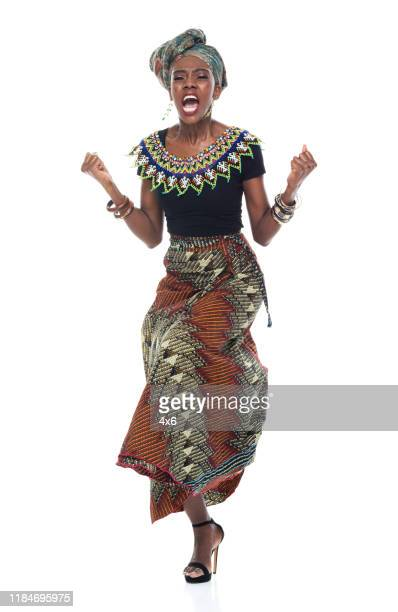 full length of 20-29 years old african ethnicity / african-american ethnicity young women / female in front of white background wearing headscarf / dress / traditional clothing who is shouting / screaming / displeased / angry - 25 29 years stock pictures, royalty-free photos & images