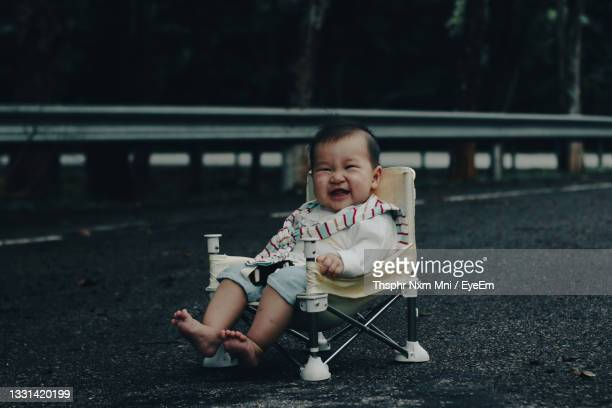 full length of a baby girl sitting outdoors - unknown gender stock pictures, royalty-free photos & images