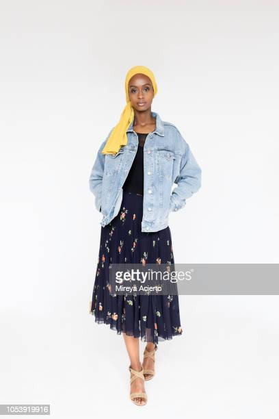 a full length of a beautiful, young muslim woman, wearing a yellow scarf, a flower dress and a blue jean jacket in studio setting. - denim dress stock photos and pictures