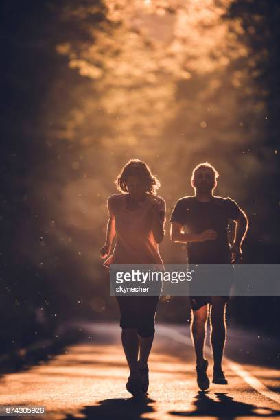 Full length of a couple running on the road at sunset.