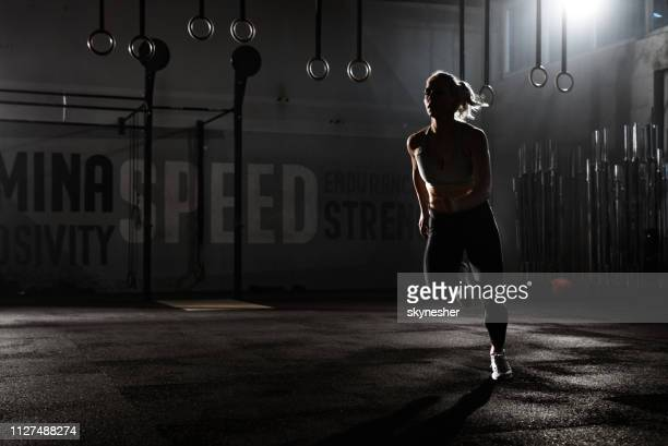 full length of a female athlete running in a health club. - athleticism stock pictures, royalty-free photos & images