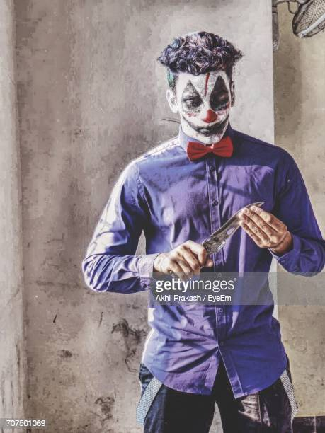 full length of a man disguised as a killer clown - scary clown makeup stock photos and pictures