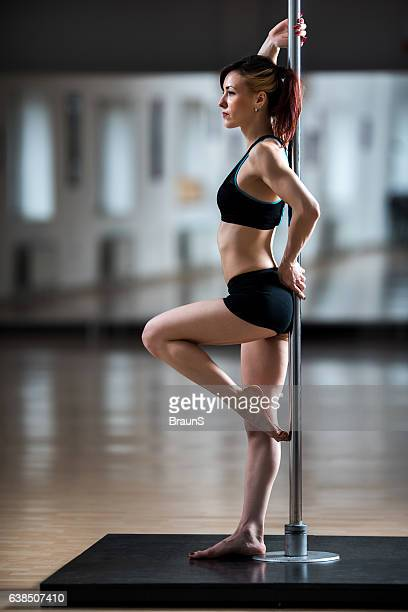 Full length of a pole dancer in a studio.