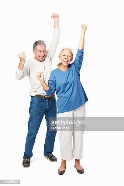 Full length of a senior couple cheering over white background