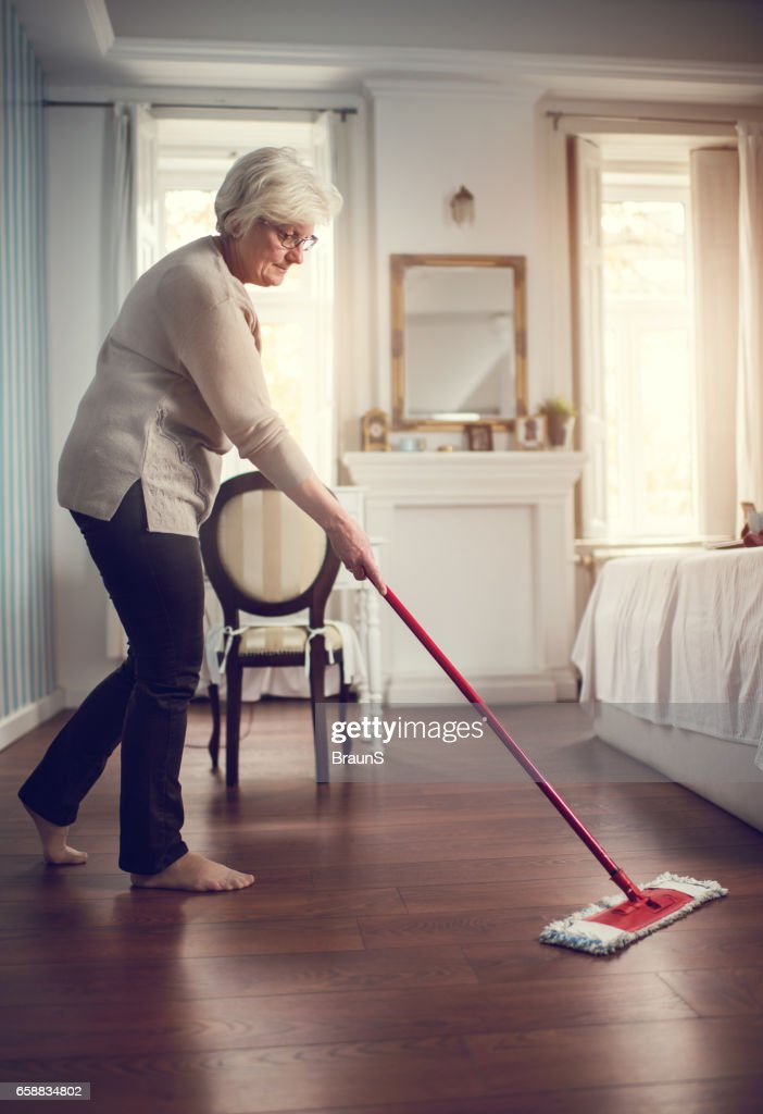 Full length of a senior woman cleaning the floor. : Stock Photo