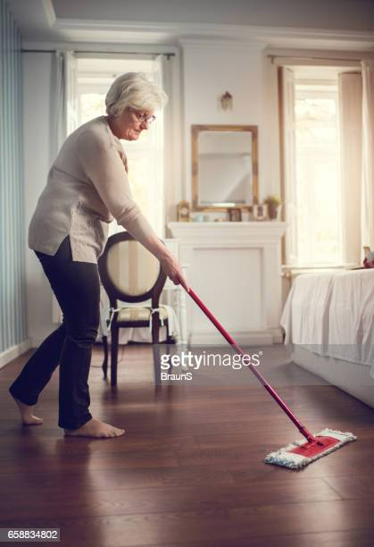Full length of a senior woman cleaning the floor.