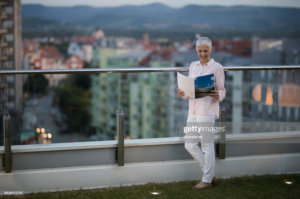 Full length of a smiling mature woman reading a magazine on a penthouse balcony. : Stock Photo