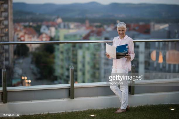 full length of a smiling mature woman reading a magazine on a penthouse balcony. - women of penthouse stock photos and pictures