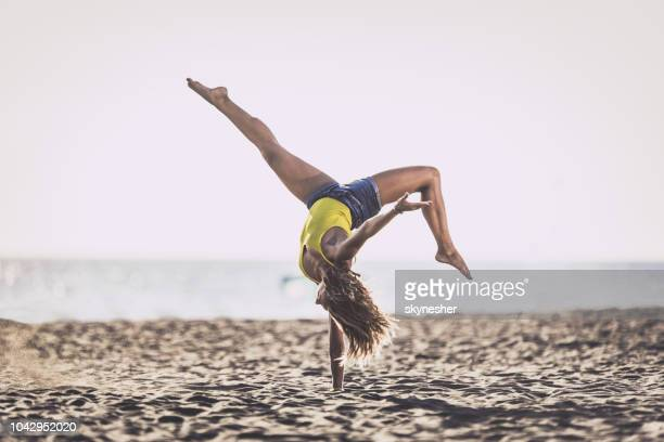 full length of a woman doing handstand on sand at the beach. - handstand stock pictures, royalty-free photos & images