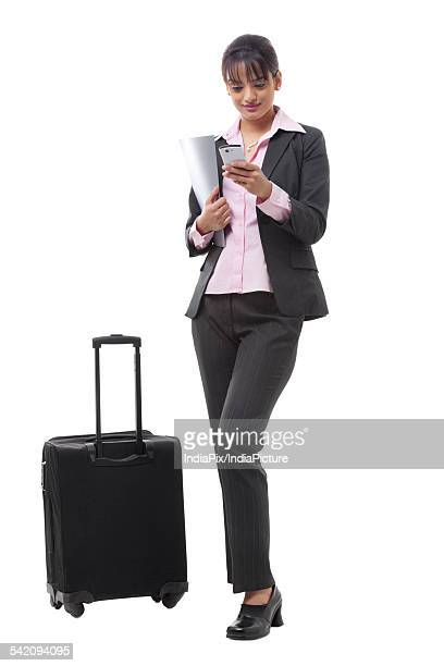 Full length of a young businesswoman with luggage reading text message