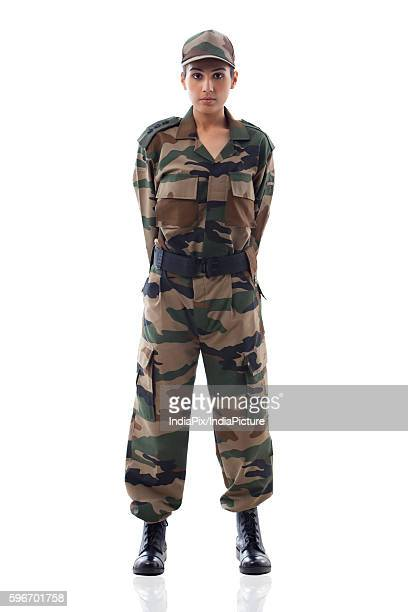 Full length of a young female soldier standing against white background