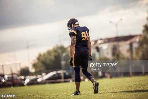 full length of american football player walking on playing field. - american football uniform stock pictures, royalty-free photos & images