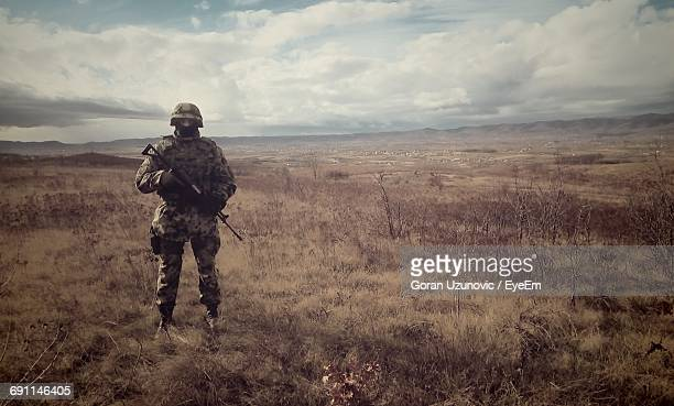 full length of army soldier standing on field against cloudy sky - army soldier stock photos and pictures