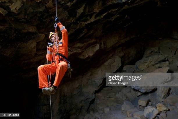 full length of athlete spelunking in cave - speleology stock pictures, royalty-free photos & images
