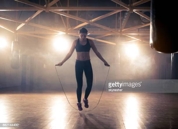 full length of athletic woman exercising with jumping rope in a health club. - skipping along stock pictures, royalty-free photos & images