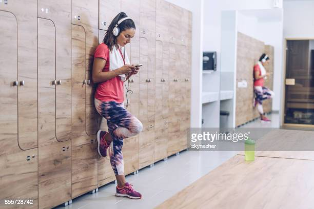 full length of athletic woman listening music at gym's locker room. - locker room stock pictures, royalty-free photos & images
