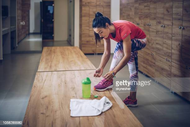 full length of athletic woman tying shoelaces in dressing room. - locker room stock pictures, royalty-free photos & images