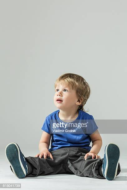 Full length of baby boy in casuals looking away over gray background