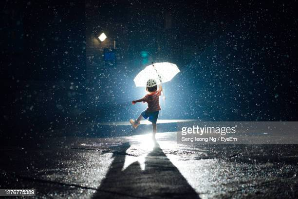 full length of baby girl holding umbrella in rain - infant with water stock pictures, royalty-free photos & images