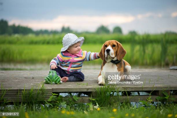 full length of baby girl sitting with dog sitting on pier against sky - one animal stock pictures, royalty-free photos & images