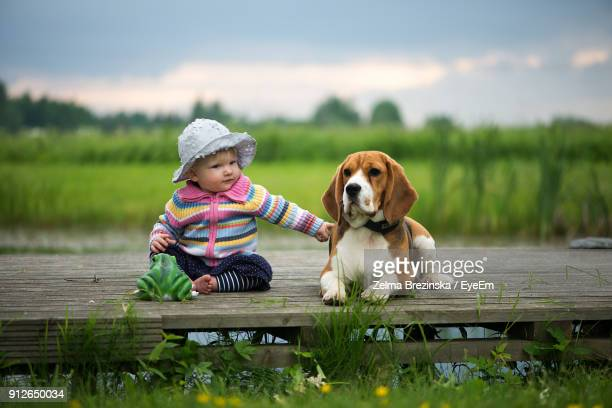 Full Length Of Baby Girl Sitting With Dog Sitting On Pier Against Sky