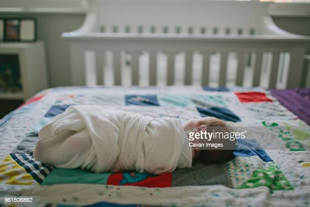 full length of baby wrapped in sheet lying on bed at home - avvolto in una coperta foto e immagini stock