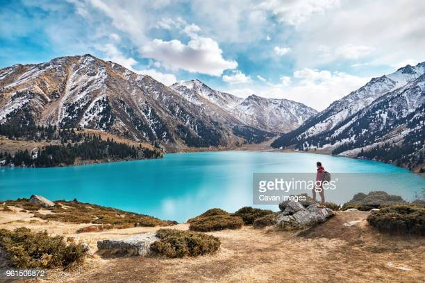 full length of backpacker looking at view while standing by lake against mountains and cloudy sky during winter - kazakhstan stock pictures, royalty-free photos & images