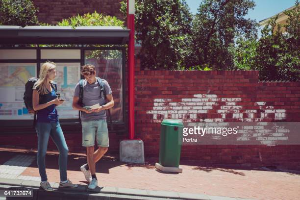 Full length of backpackers waiting at bus stop