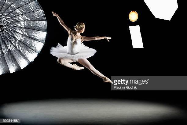 Full length of ballerina performing in mid-air at studio