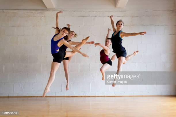 full length of ballet dancers in studio - friendly match stockfoto's en -beelden