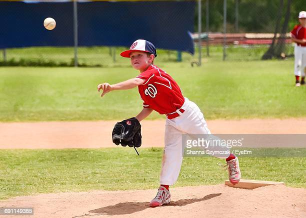 full length of baseball pitcher throwing ball - baseball pitcher stock photos and pictures