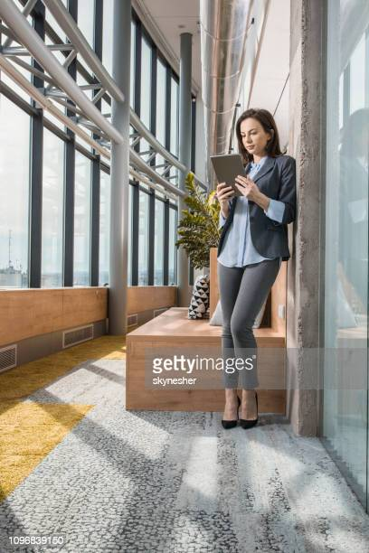 full length of beautiful businesswoman using digital tablet in the office building. - economist stock pictures, royalty-free photos & images